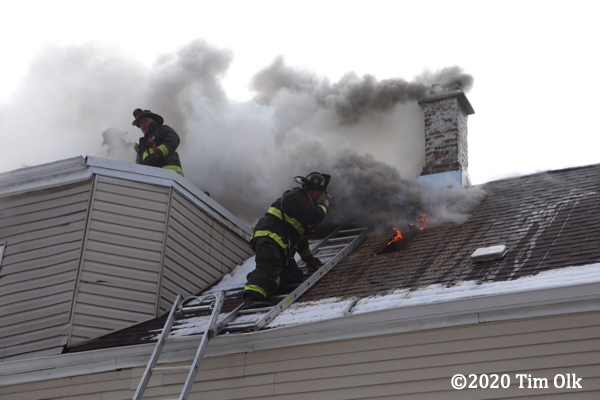Firefighter vents roof on attic ladder for safety