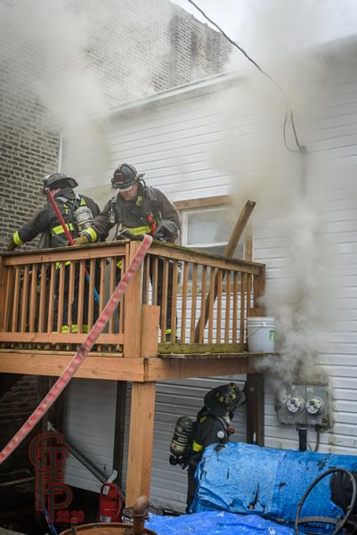 Firefighters on back deck with smoke