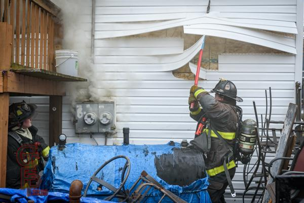 Firefighter pulls siding off house