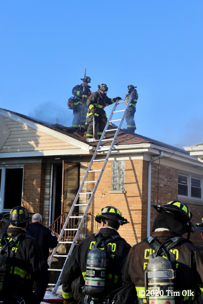 Firefighters on roof of a house fire