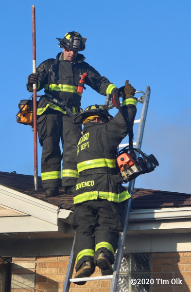 Firefighters descend roof from a ladder