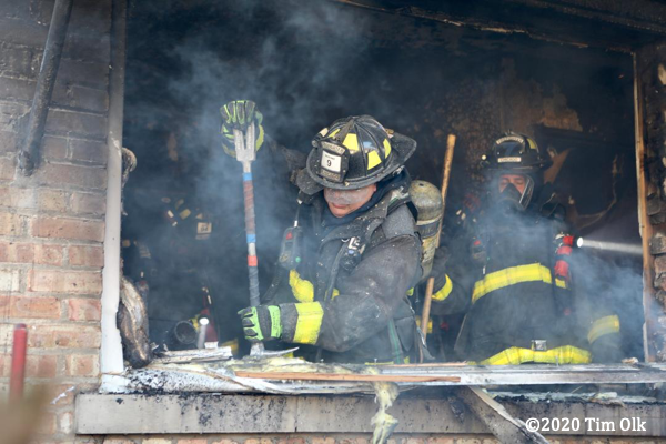 Firefighters overhaul after a house fire