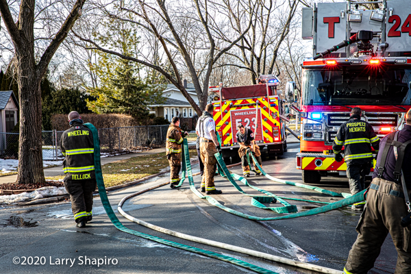 Firefighters drain hose after a fire