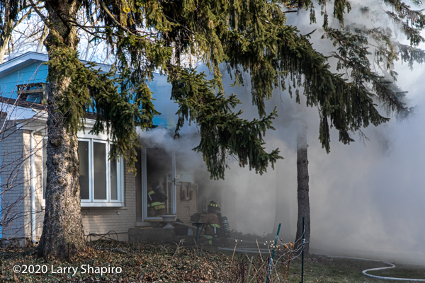 Firefighters enter burning house with hose