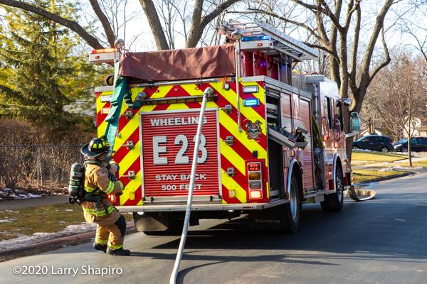 Firefighter pulls hose off of engine