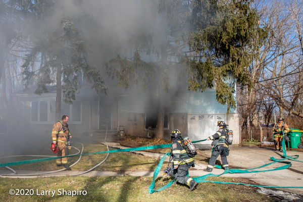 Firefighters prepare a second line during a house fire