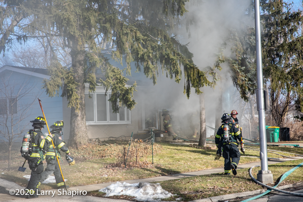 Firefighters approach house fire with tools