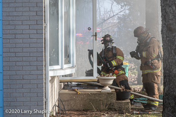 Firefighters prepare to take a line into a house