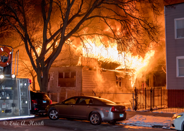 flames engulf the roof of  house at night