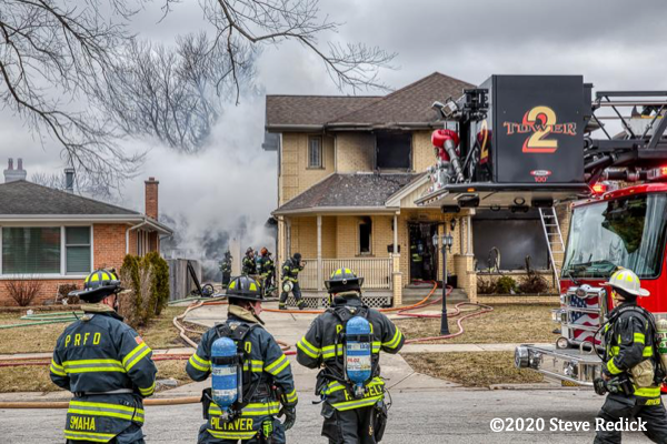 Firefighters stand by at house fire