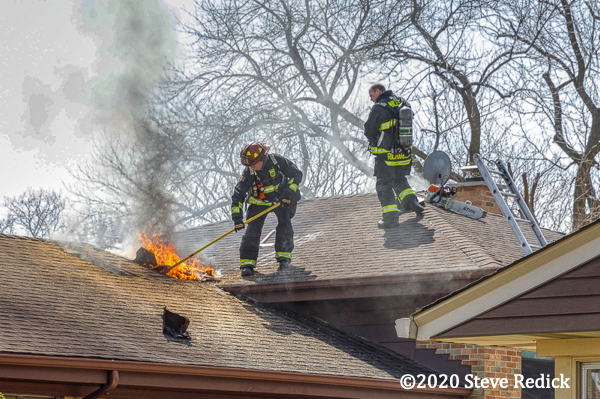 Firefighters on roof of a house