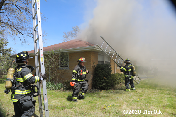 Firefighters with ground ladders at house fire