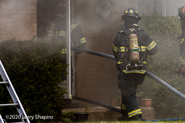 Firefighters enter house with hose line