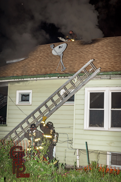 Firefighters raise a ground ladder