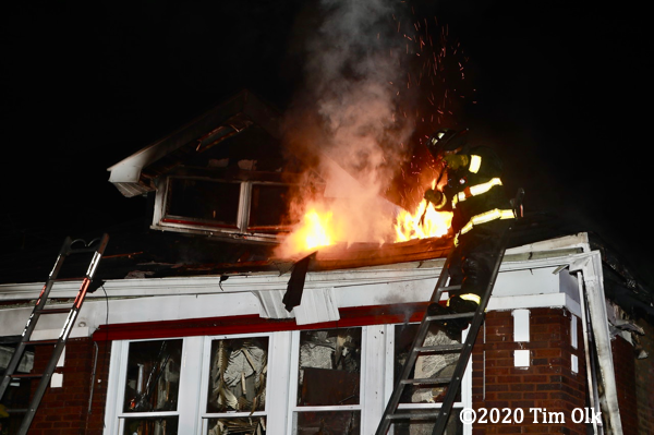Firefighter on ladder with fire showing