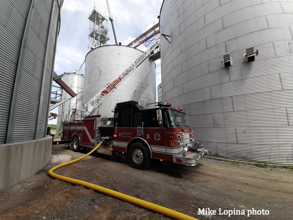 aerial ladder stretches to grain bin