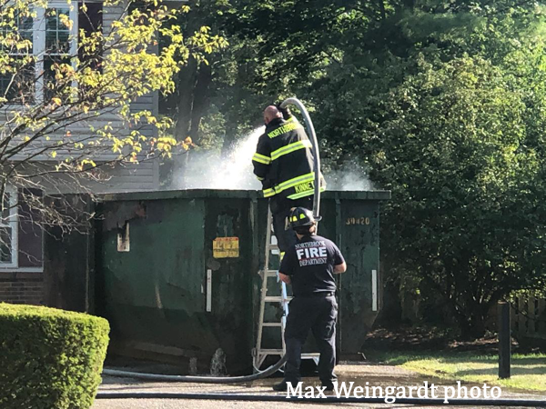 Firefighters extinguish a dumpster fire