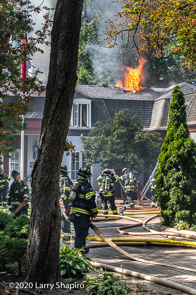 Firefighters pull hose to battle a house fire