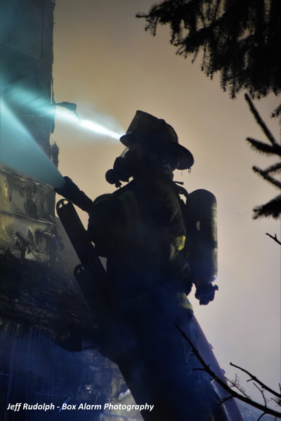 Firefighter silhouette with hose line on a ladder