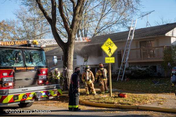 Firefighter on ground ladder vents window with smoke #EONE Strength