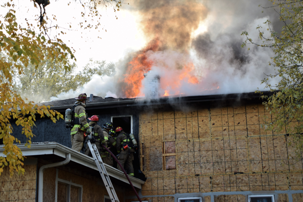 heavy flames and smoke from roof of a house