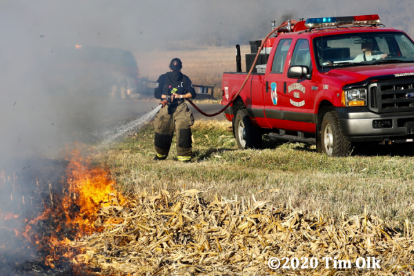 Firefighters douse field fire from brush truck