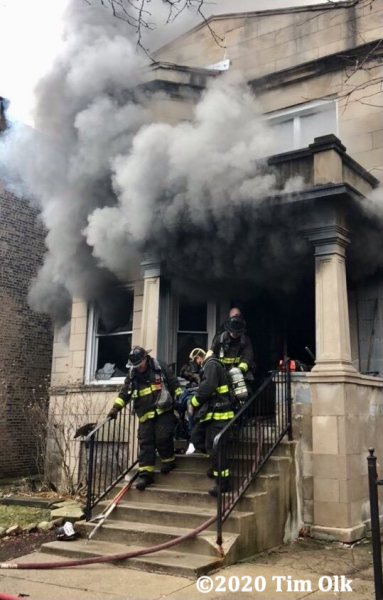 Firefighters carry victim from house fire