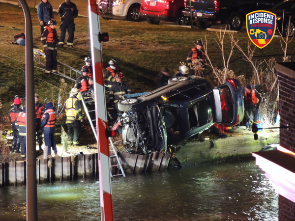 Milwaukee Firefighters at the scene of a overturned car by the Milwaukee River