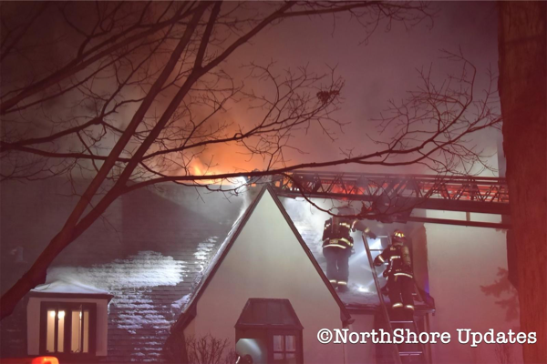 flames through the roof of a house at night