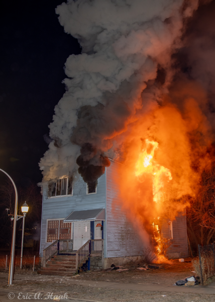 two-story. house totally engulfed by fire at night