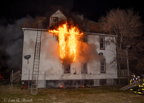 flames blow out of a house at night