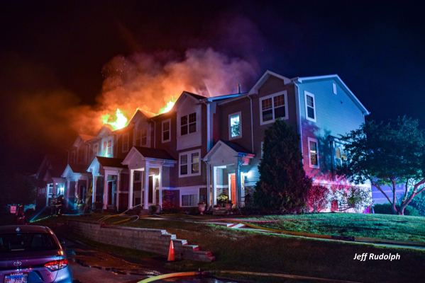 flames through the roof of a townhouse at night