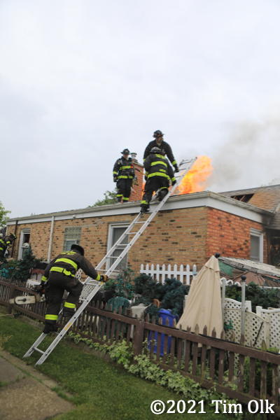 Firefighters climb ladder to roof with flames