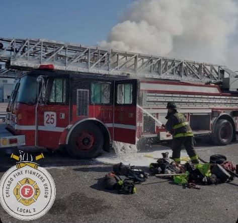 Chicago Firefighter extinguishes a fire in a spare ladder truc