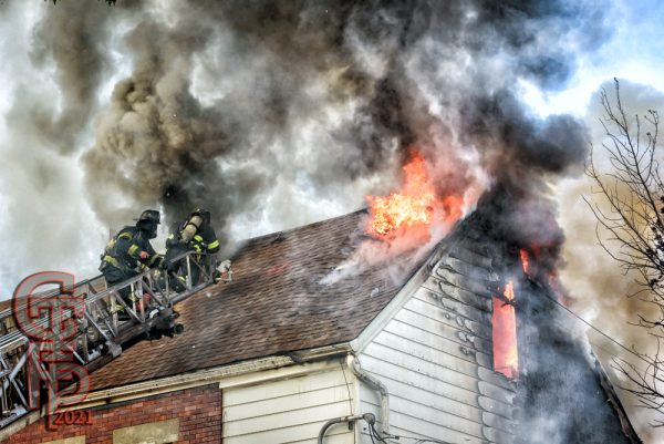 smoke and flames from roof of building fire