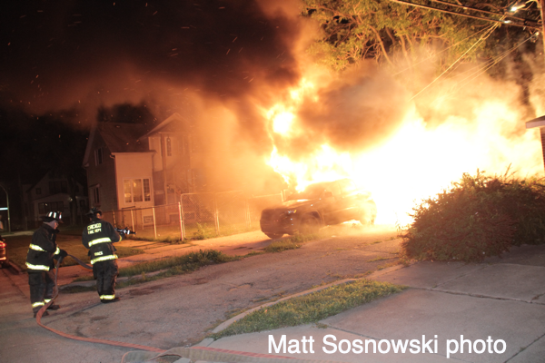 flames engulf a car and garage at night