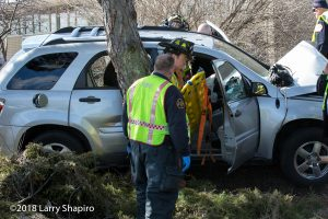 Firefighters attend to car crash victim
